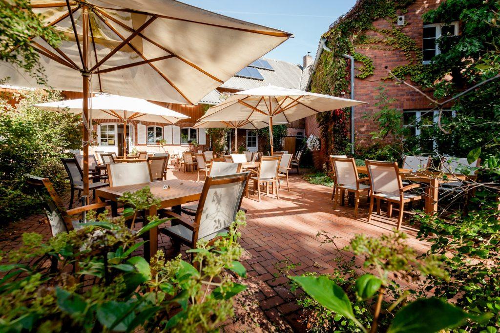 Terrasse mit weißen Sonnenschirmen und vier Holztischen samt Stühlen.