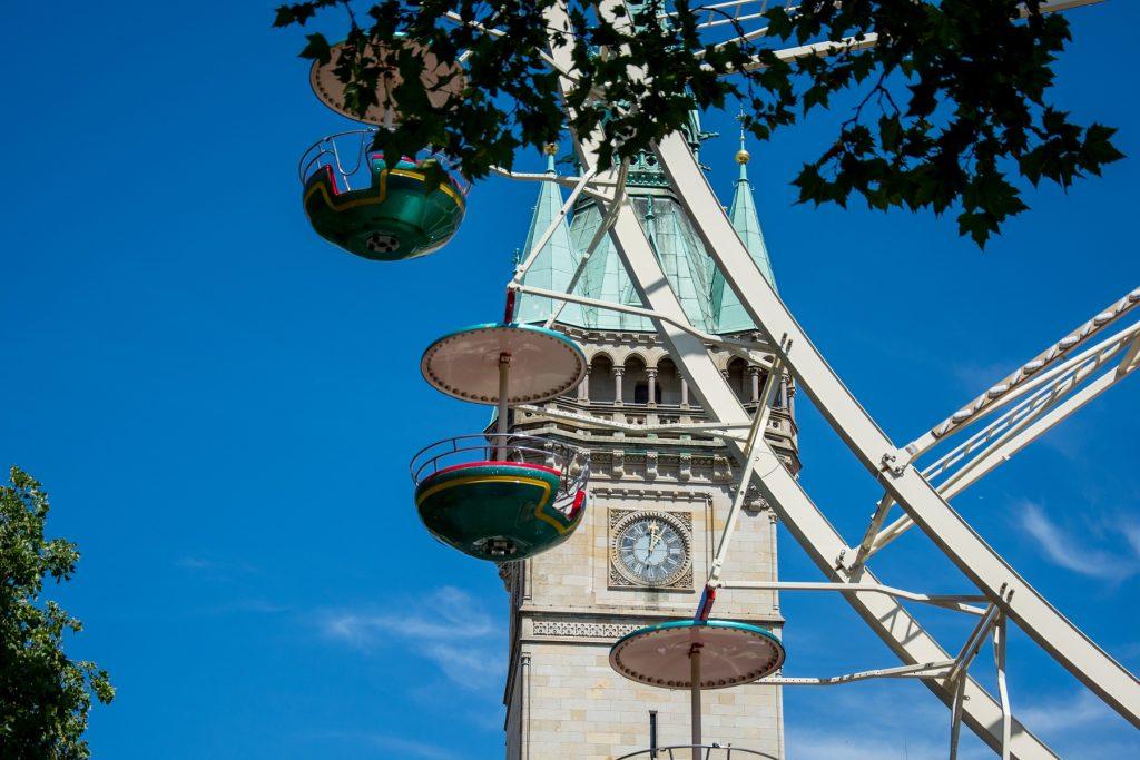 Vor dem Rathausturm in Braunschweig sind Gondeln eines Riesenrades zu sehen.