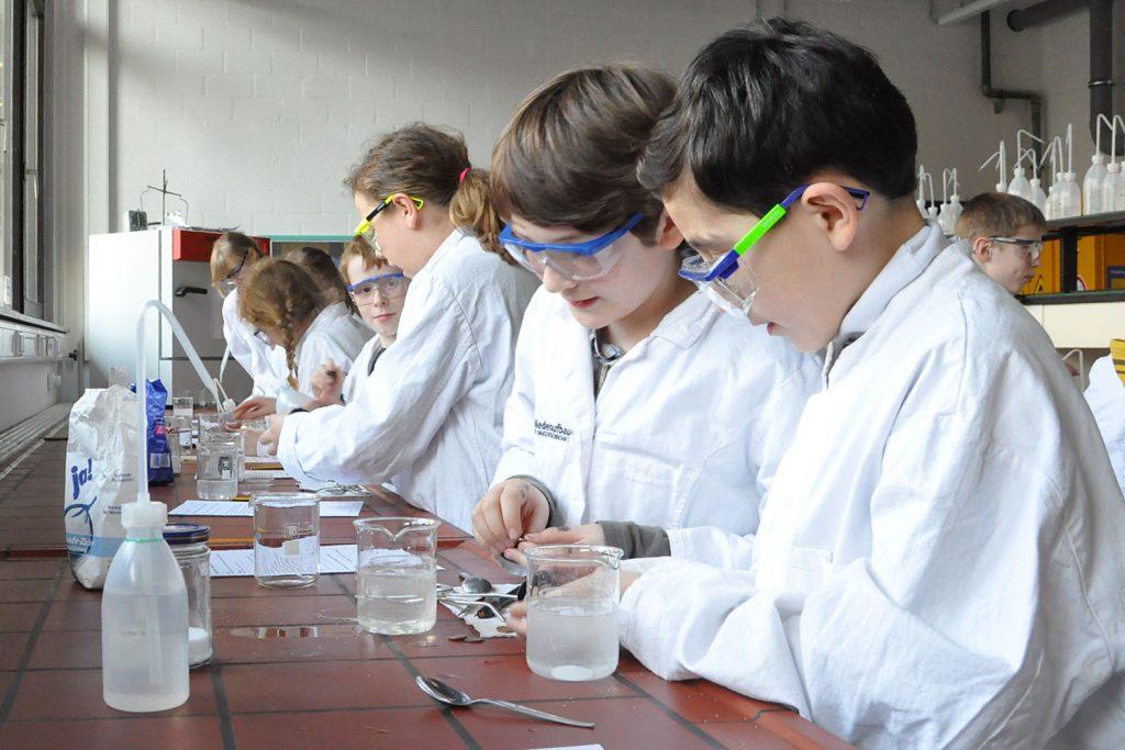 Schüler mit weißen Kitteln beim Experimentieren