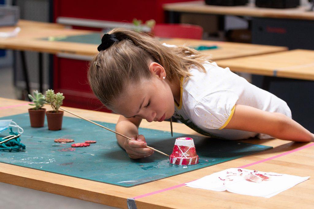 Ein Mädchen beugt sich über einen kleinen Topf und bemalt ihn mit Farbe.