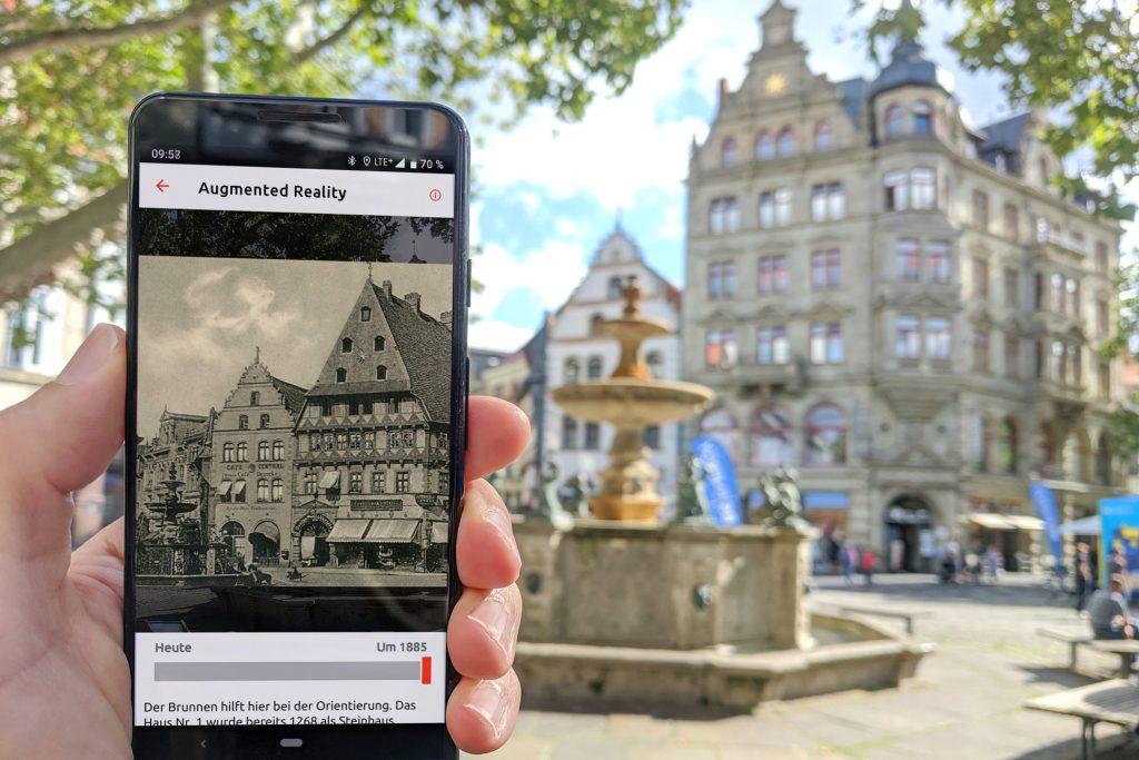 Ein Handy zeigt ein historisches Bild vom Kohlmarkt. In der rechten Bildhälfte ist der Kohlmarkt heute zu sehen.