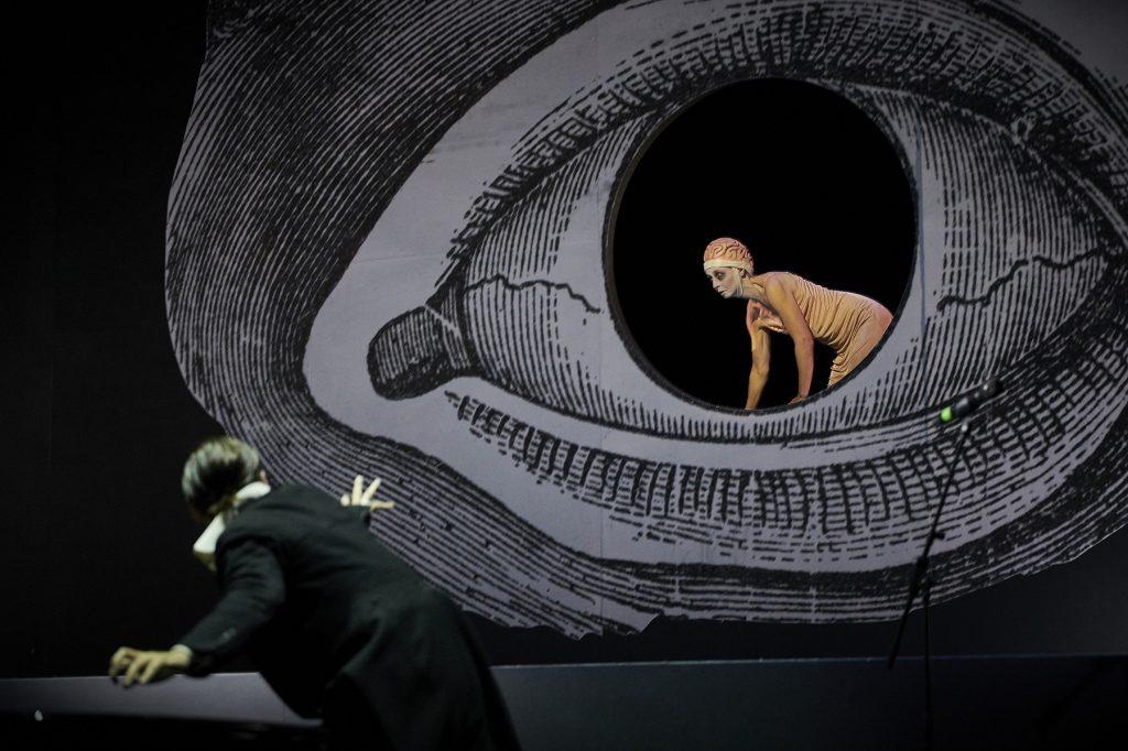 Auf der dunklen Bühne ein überdimensionales, gezeichnetes Auge, die Pupille ist ein Loch, in das eine Frau kriecht. Ein Mann davor, der sich zu dem Auge hindreht.