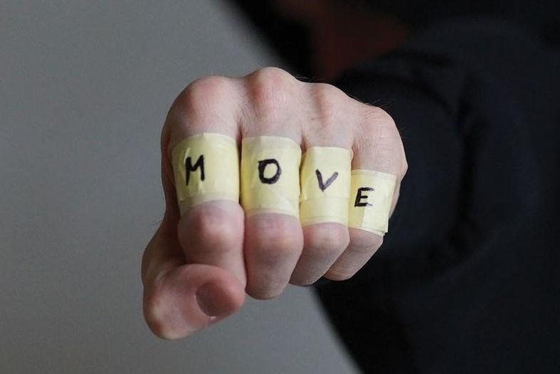 Eine Hand zur Faust geballt, die Fingerrücken sind mit Kreppband umwickelt, auf jedem Finger steht ein Buchstabe: M, O, V, E