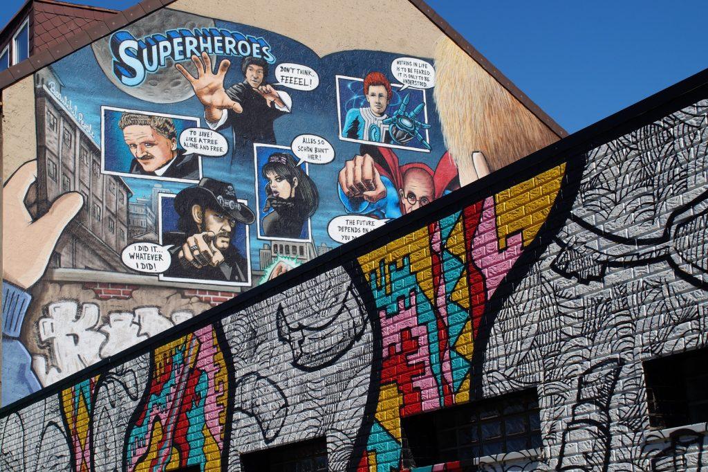 """Ein Street-Art-Gemälde an einer Hauswand. Zu sehen sind verschiedene Superhelden mit Sprechblasen in denen Zitate wie """"I did it ... whatever I did"""" oder """"Don´t talk, feeeel!"""" stehen. Einige Sprechblasen sind unleserlich."""