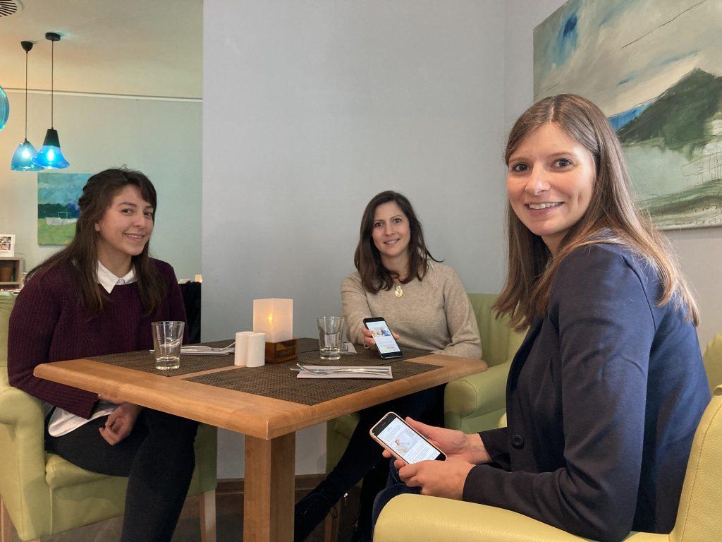 Drei Frauen sitzen an einem Tisch, zwei halten ihr Handy in der Hand auf der die App Babybauch geöffnet ist.