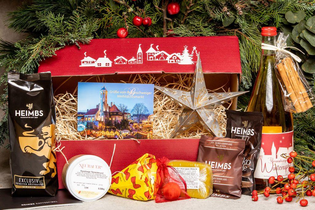 Vor Tannengrün ist eine rote Pappbox mit weißen weihnachtlichen Motiven und  verschiedene Waren aufgestellt: Glühweinflasche, eine Tüte gebrannte Mandeln, ein Papierstern, ein Marzipanblock, Mummeleberwurst, Kakao und Kaffee und eine Mandarine.