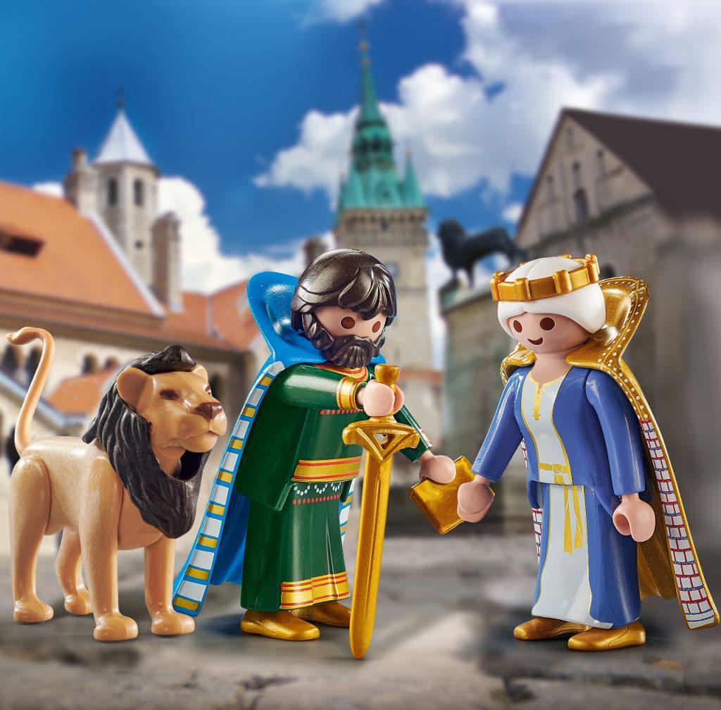 Drei Playmobilfiguren, ein Löwe, ein Mann mit königlichem Umhang, Schwert und goldenem Buch und eine Frau mit Krone und Umhang.