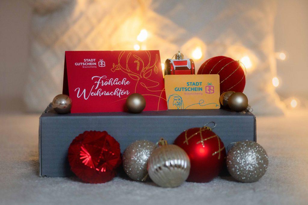 """Auf einem Karton steht eine Grußkarte """"Frohe Weihnachten"""", daneben die Gutscheinkarte des Stadtgutschein Braunschweig. Darum herum sind Weihnachtskugeln dekoriert."""