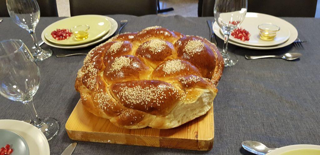In der Bildmitte ein rundes Brot mit Sesam bestreut.