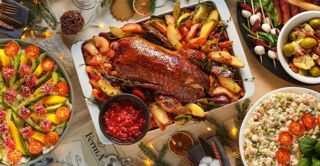 Verschiedene Speisen, in der Mitte eine gebratene Ente.