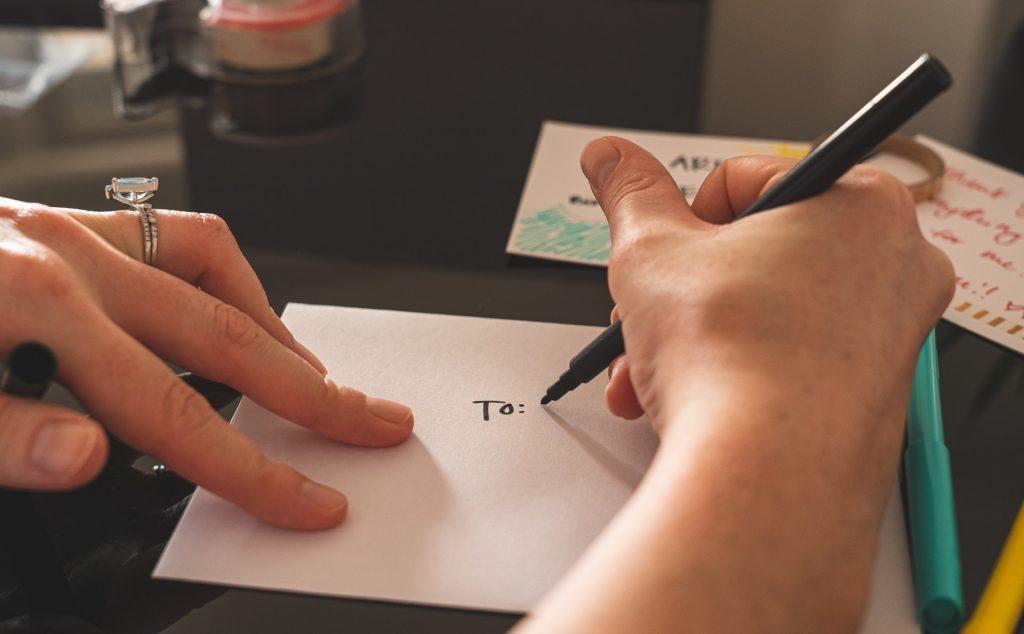 Weibliche Hände beschriften einen Briefumschlag