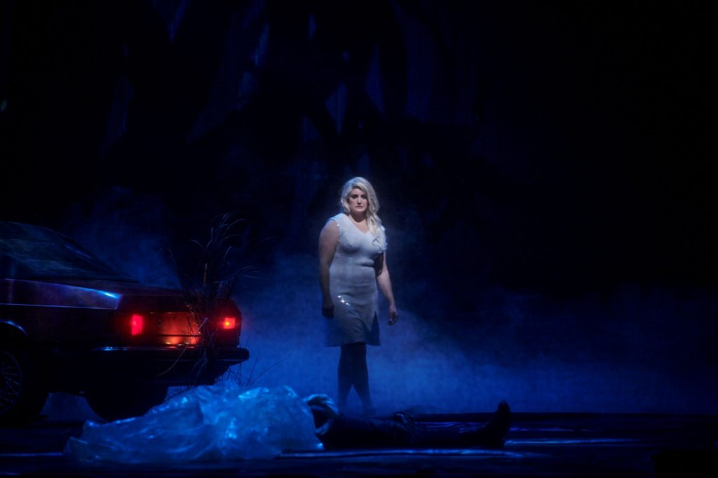 Eine Frau steht neben einem Auto im Nebel.