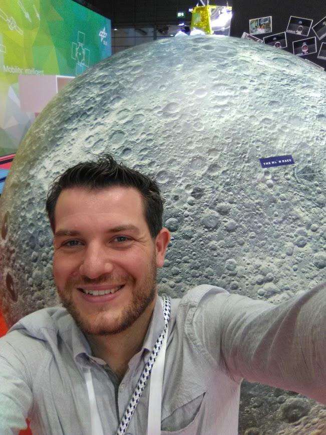 Ein Mann mit dunklen Haaren lächelt in die Kamera. Er trägt einen grauen Pullover und posiert vor einem Modell des Mondes.