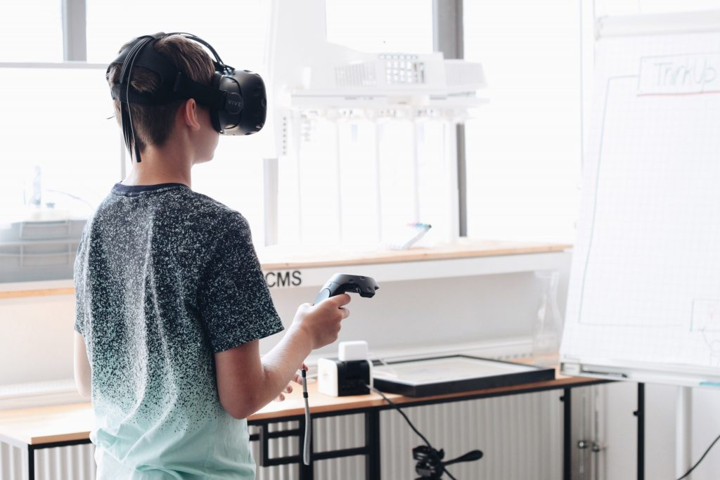 Ein Junge im T-Shirt steht in einem Klassenraum. Er hat eine VR-Brille auf dem Kopf und hält einen Controller in der Hand.