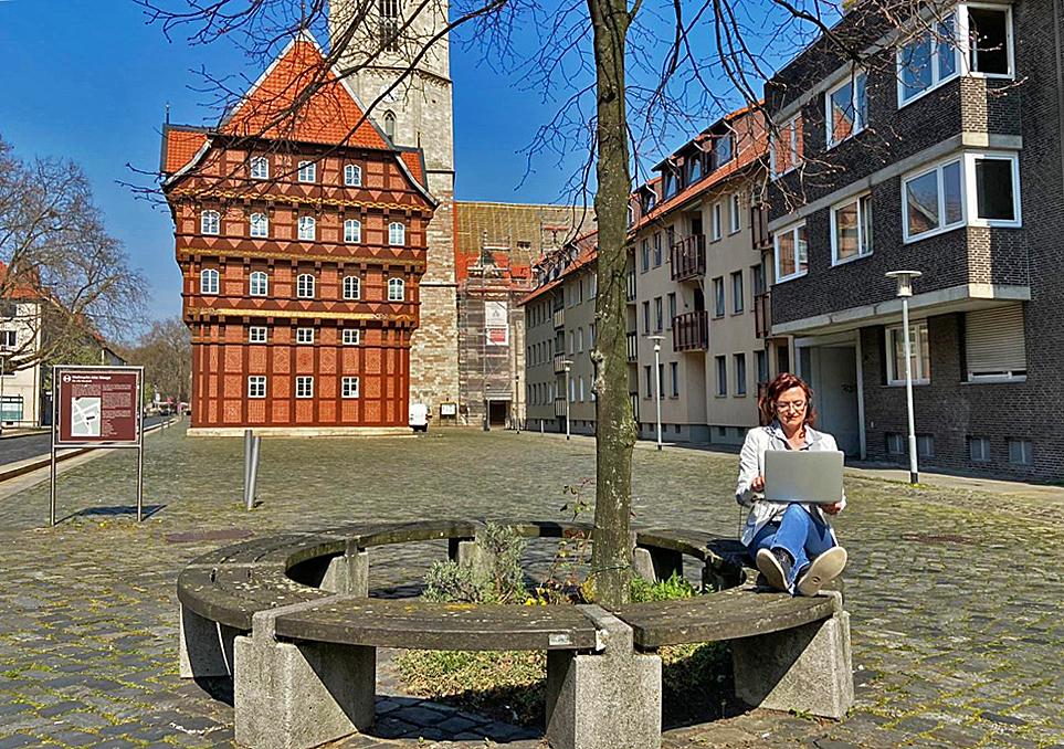 Eine Frau sitzt mit einem Laptop auf einer Bank vor der Alten Waage in Braunschweig.