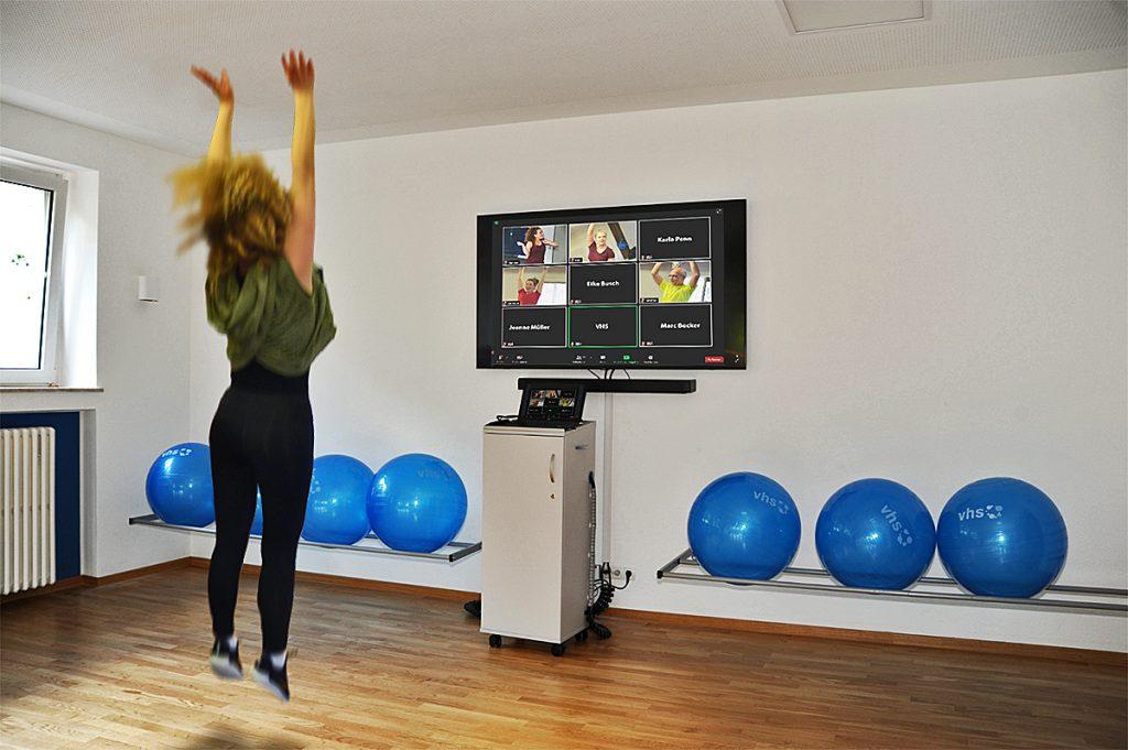 Eine Frau springt vor einem Bildschirm.
