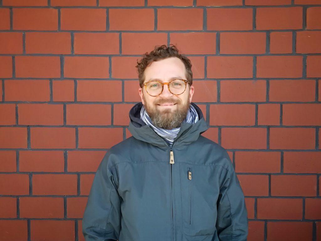 Ein junger Mann in blauer Jacke grinst freundlich in die Kamera.