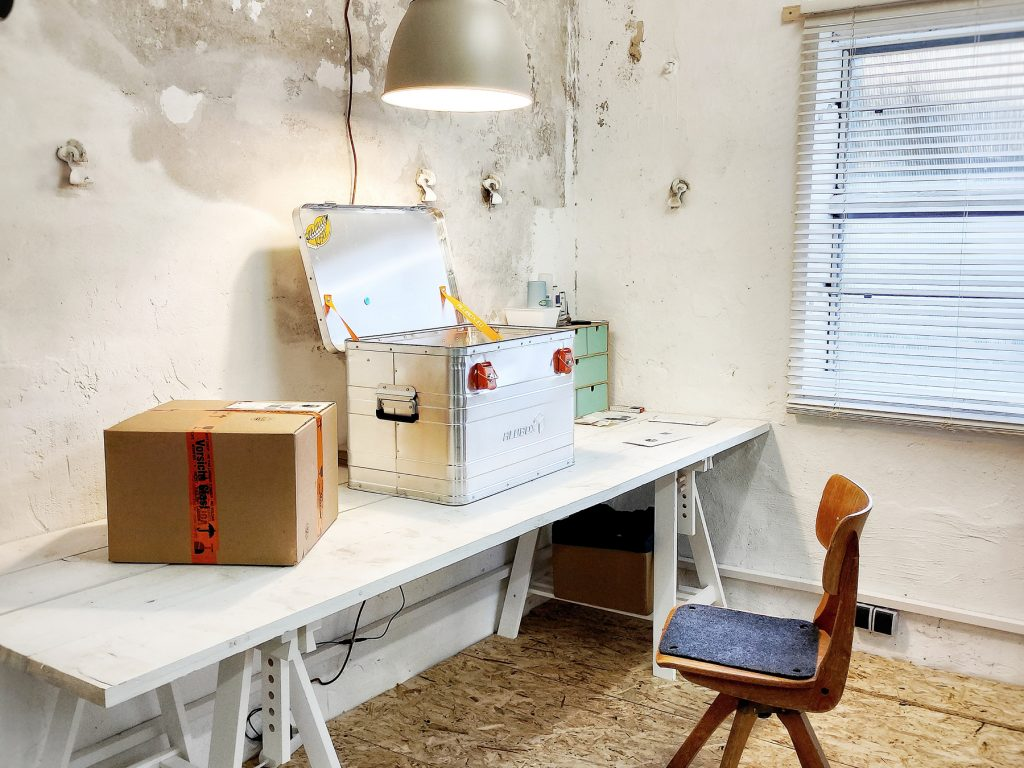 Ein weißer Schreibtisch steht in einem Raum, auf dem Schreibtisch ein versandfertiger Karton, daneben eine Spachtelkiste