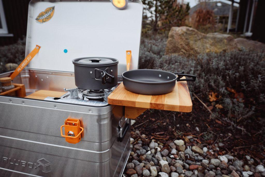 Eine Aluminiumbox, an deren Seite ein Brettchen geklemmt ist. Auf dem Brettchen steht eine Camping-Pfanne, daneben auf dem Campingkocher in der Box ein Topf.