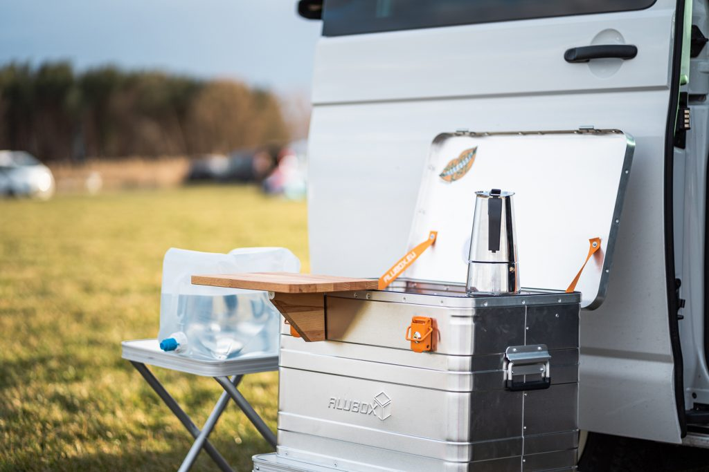 Eine geöffnete Spachtelkiste vor einer weißen Bullitür. Auf dem Kocher steht eine Kaffeekanne, das Arbeitsbrett ist an der Kiste befestigt.