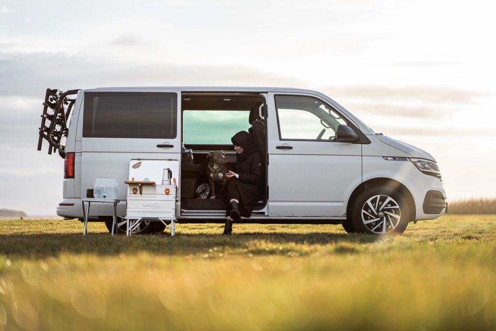 Ein weißer VW Bulli auf einem Feld. In der offenen Tür sitzt eine Frau mit einem Hund. Vor dem Bulli ist die Spachtelkiste aufgestellt.