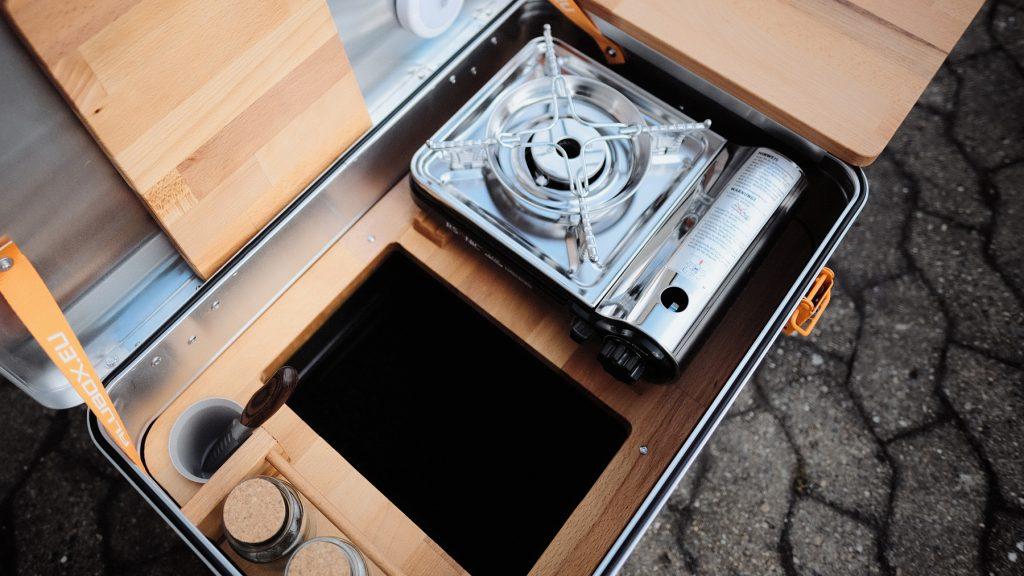 Eine aufgeklappte Alubox, in der sich eine Abdeckung aus Buchenholz, ein Campingkocher und drei Gewürzgläser befinden.