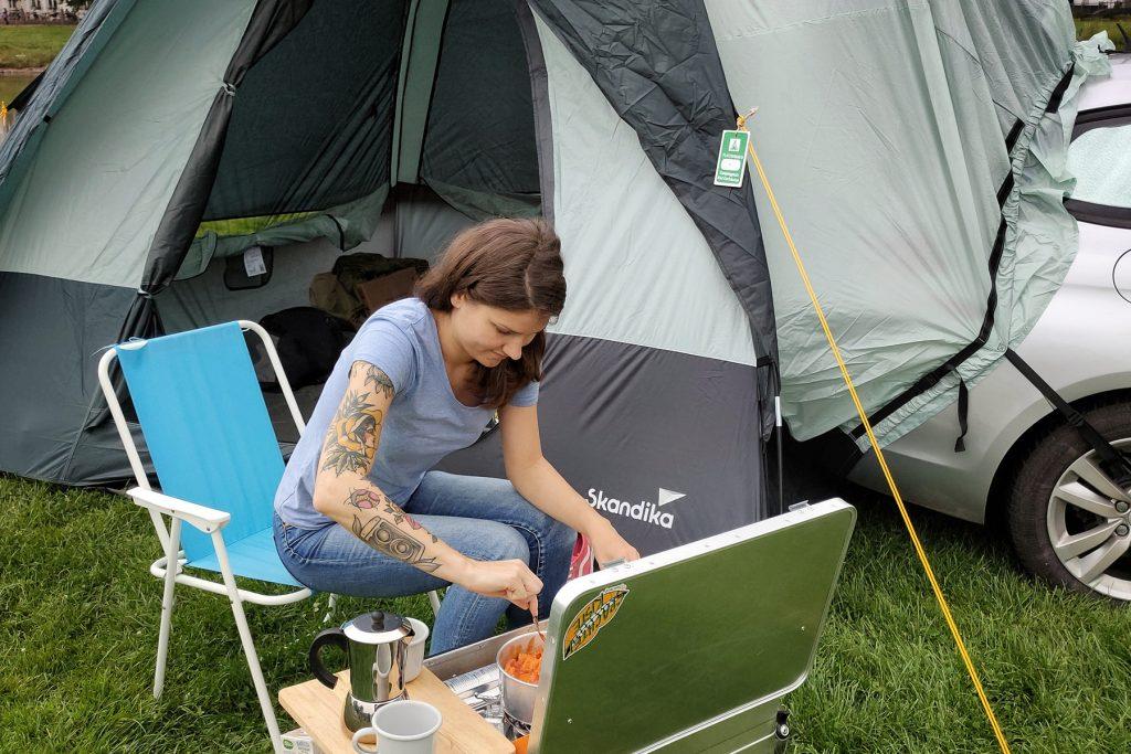 Eine junge Frau sitzt vor einem Zelt. Vor ihr die aufgeklappte Spachtelkiste. Auf dem Brettchen am Rand stehen zwei Becher und eine Kaffeekanne. Die Frau rührt in einem Topf, der in der Box steht.