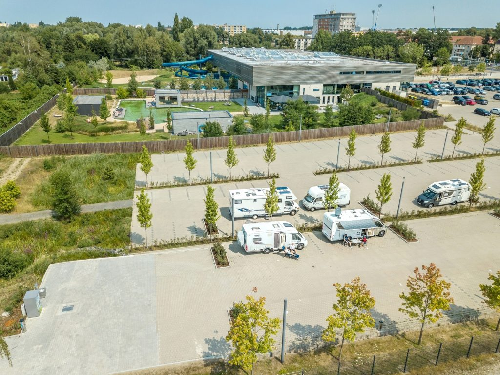 Das Foto ist aus der Luft aufgenommen. Man sieht den Wohnmobilstellplatz, dahinter den Außenbereich des Schwimmbades sowie die Wasserrutsche, das Schwimmbad und den Parkplatz davor.