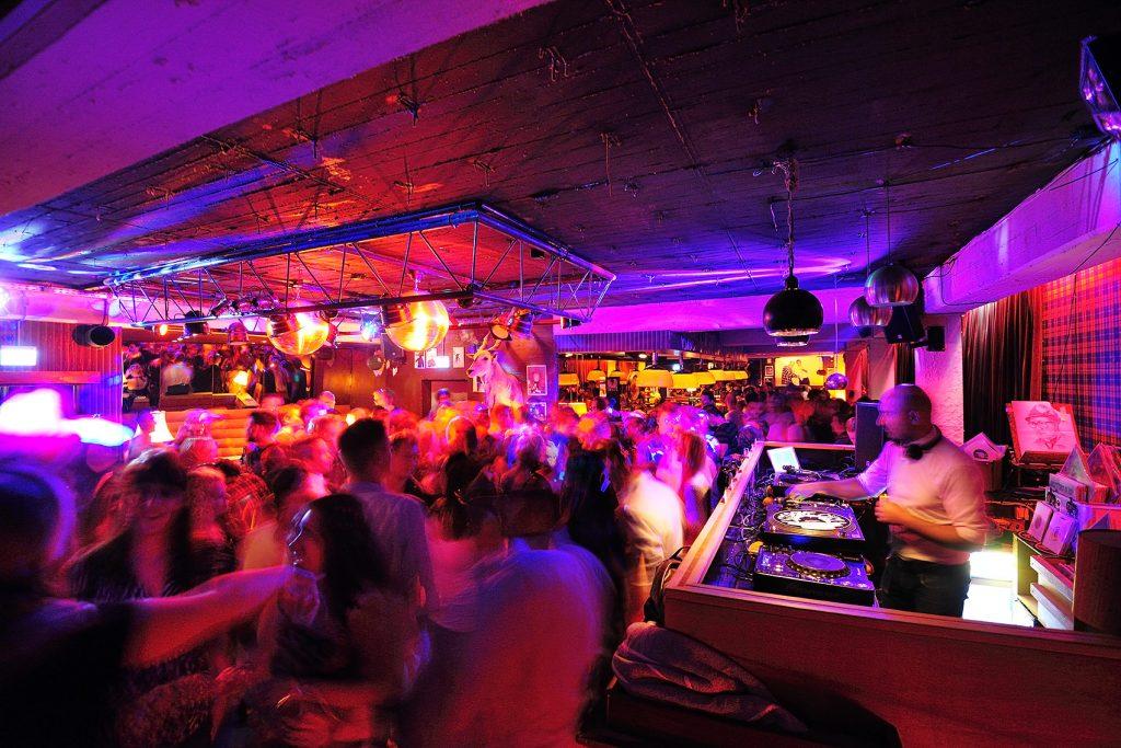 Ein Raum, der lila, orange beleuchtet ist und sonst eher schummrig. Rechts ein DJ-Pult davor Menschen, die sich zu der Musik bewegen. Ihre Körper sind vom Tanzen verwischt.