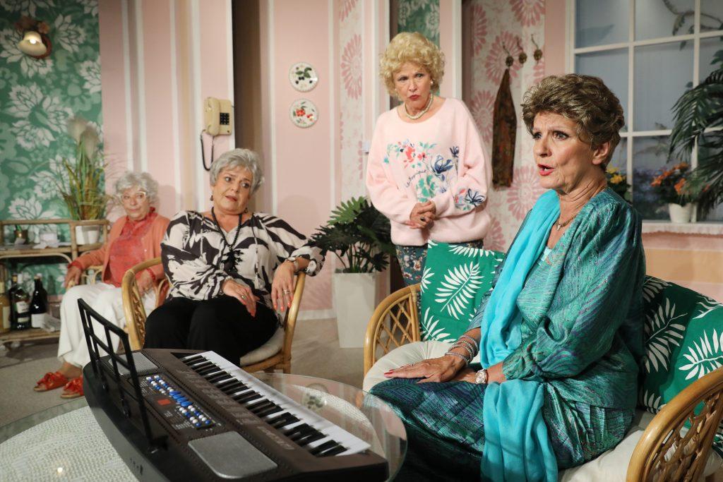 eine ältere Dame sitzt im Vordergrund an einem Keyboard, dahinter stehen und sitzen drei weitere ältere Damen.