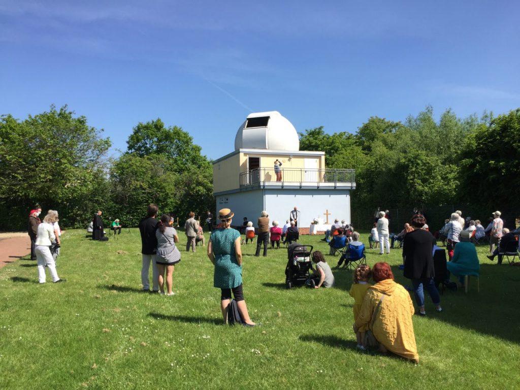 Im vorderen Bildteil stehen allein oder zu zweit Astronomie-Freunde und schauen zur Sternwarte, die sich im hinteren Bildteil befindet.