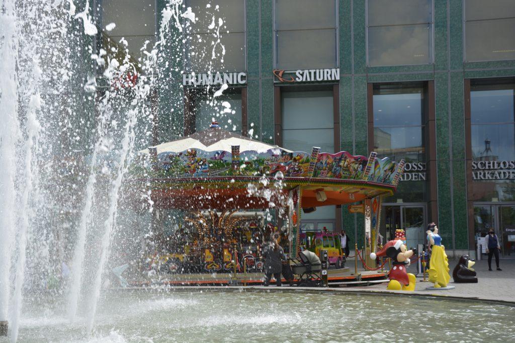 Im Vordergrund ist der Ritterbrunnen in Braunschweig zu sehen, dahinter ein Kinderkarussell.