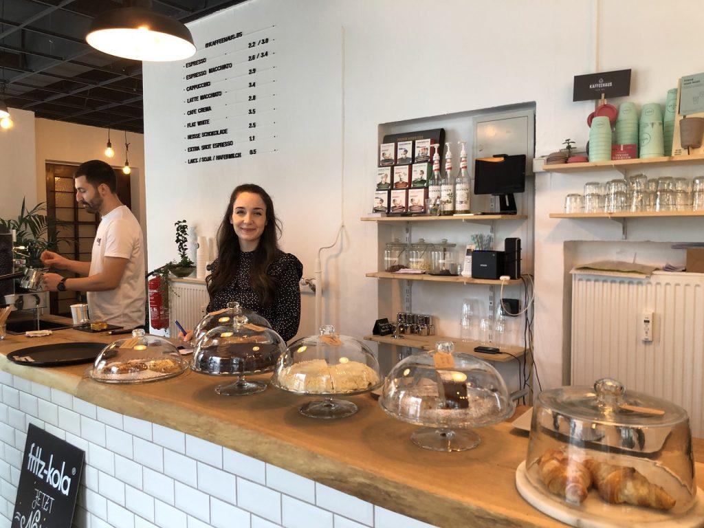 Hinter der Theke steht eine Frau, die in die Kamera guckt. Auf der Theke stehen verschiedene Kuchen und Gebäckteile. Im Hintergrund macht ein Mann Kaffee an einer Siebträgermaschine.