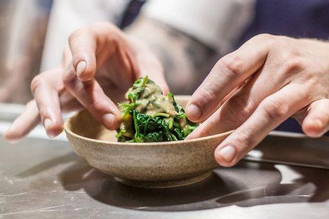 zwei Hände richten ein wenig Salat in einer kleinen Schüssel an.