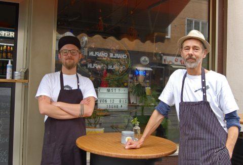 Zwei Männer stehen vor einem Schaufenster an einem Stehtisch.