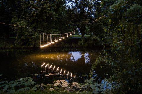 Leuchtstoffröhren, die wie eine Treppe über einem fluss schweben.