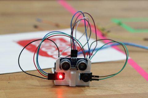 Eine Platine mit zwei Kameras, die wie Augen aussehen steht auf einem Tisch. Die Kameras sind mit bunten Kabeln mit der Platine verbunden.