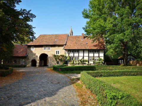 Ein Weg führt zu einem dunklen Tor in einem mittelalterlichen Gebäude.