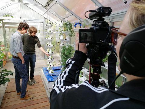 Schulterblick über eine junge Frau, die eine Kamera hält. Im Hintergrund zwei junge Männer, die auf eine futuristische Rankhilfe für Pflanzen zeigen.