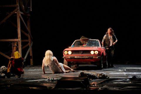 Zwei Menschen neben einem Auto auf einer Bühne.