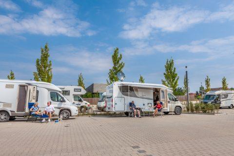 Zwei Wohnmobile. Vor dem linken wohnmobil sitzt ein älteres Paar mit Hund. Vor dem rechten Wohnmobil sitzt ein junges Paar an einem Campingtisch.