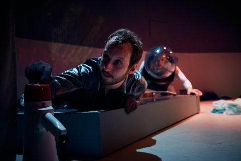 Ein Mann liegt auf einer Plattform und schaut auf eine Teekanne. Ein zweiter Mann liegt dahinter, dieser Mann hat einen Astronautenhelm auf dem Kopf.